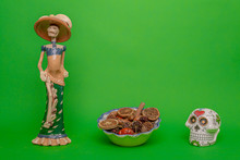 Calavera De La Catrina Statuette, Mexican Symbol Of Day Of The Dead, Next To A White Skull And A Bowl With Dried Fruits, On A Uniform Green Studio Background