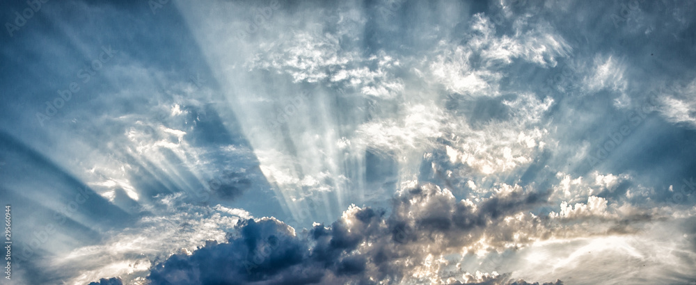 Fototapeta the sun's rays breaking through the clouds in straight lines against the sky and thunderclouds