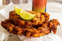 Two Delicious Conch Fritters With Sliced Limes Served As An Appetizer.