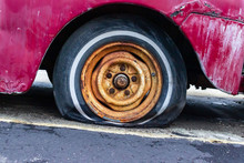 A Flat Tire On A Red Antique Pickup Truck.