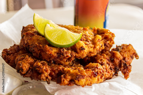 Two delicious conch fritters with sliced limes served as an appetizer Fototapeta