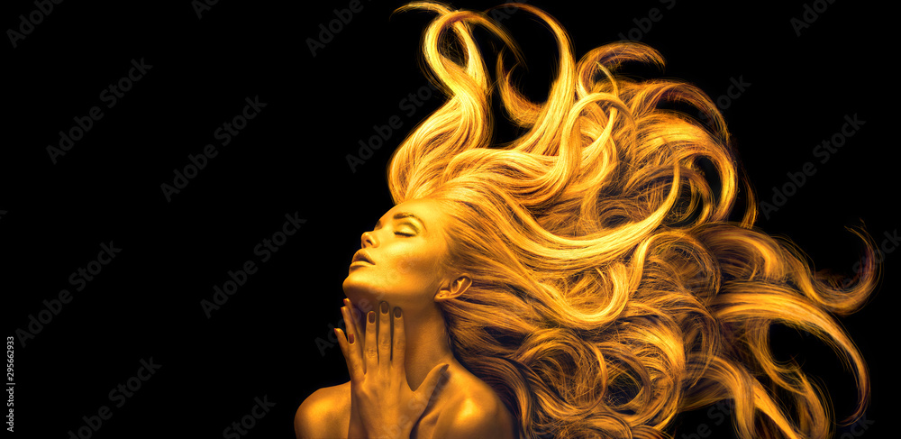 Gold Woman. Beauty fashion model girl with Golden make up, Long hair on black background. Gold glowing skin and fluttering hair. Metallic, glance Fashion art portrait, Hairstyle. Fashion art design