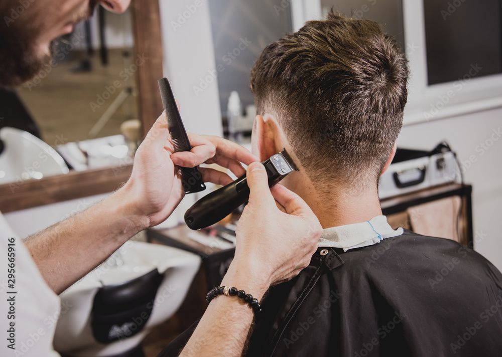 Fototapeta Young man with trendy haircut at barber shop. Barber does the hairstyle and beard trim.