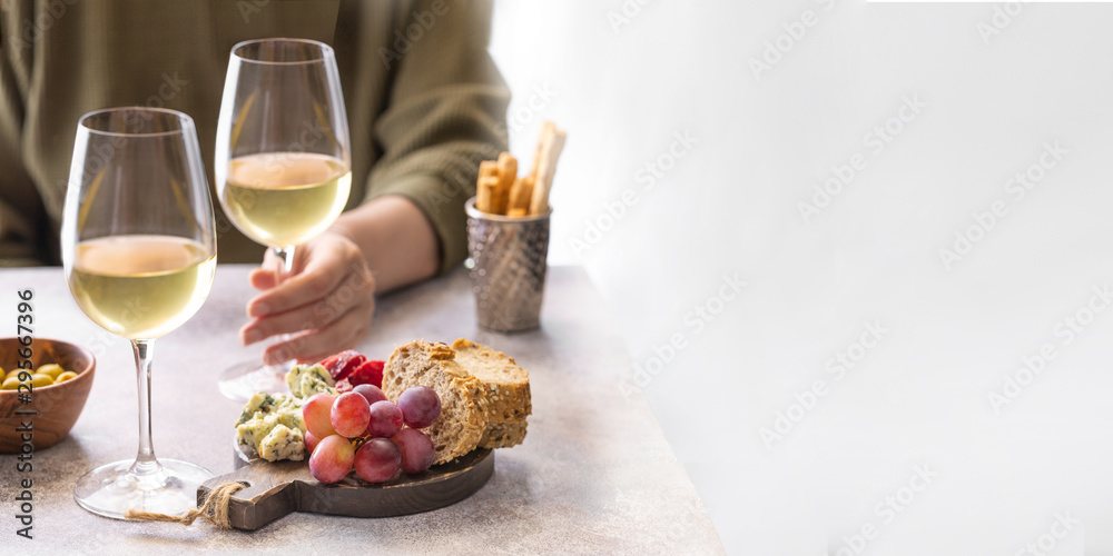 Fototapety, obrazy: .Woman holding glass of white wine in the restaurant. Different snacks, Blue cheese, olives, baguette slices and cured meat. Tasting party lifestyle background for Banner with copy space.