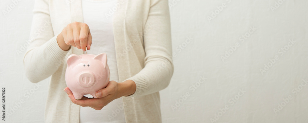 Fototapety, obrazy: woman hand putting money coin into piggy for saving money wealth and financial concept.