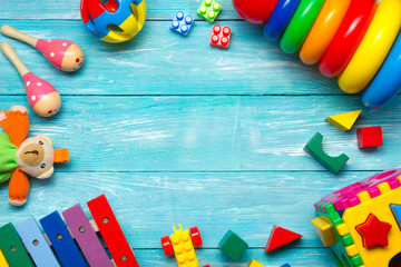 Colorful kids toys frame on wooden background. Top view. Flat lay. Copy space for text.