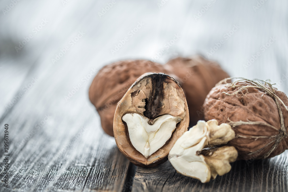 Fototapety, obrazy: Walnut in open form on a wooden background, close-up .