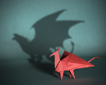 Concept Of Hidden Potential. A Paper Figure Of A Dragon  That Fills The Shadow Of A Strong Dagon. 3D Illustration