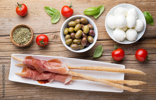 Raw ham and breadsticks with cherry tomatoes, taggiasca olives and small mozzarella. Top view.
