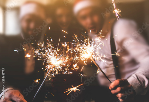 sparklers in the foreground. Beautiful young people at a corporate party. New Year celebration. Club party with friends - 295683775