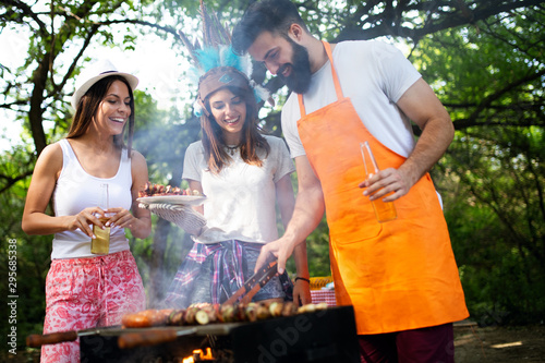 obraz lub plakat Friends having fun in nature doing bbq
