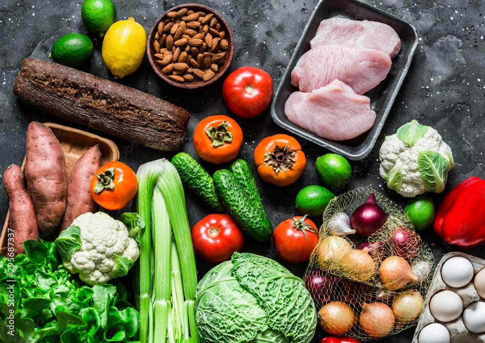 Fototapety, obrazy: Healthy diet food set. Fresh organic vegetables, fruits, turkey meat, eggs, whole wheat bread on a dark background, top view.  Homemade menu planning