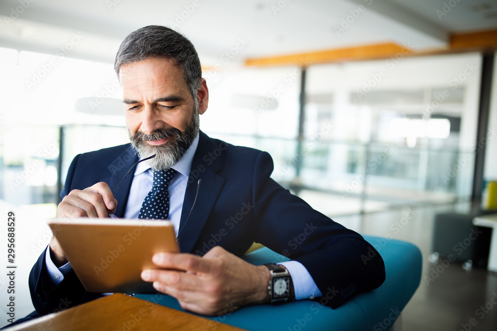 Fototapeta Elegant business multitasking multimedia man using devices