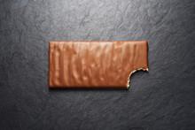 Bitten Milk Chocolate Bar On Black Slate Background
