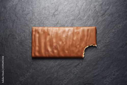Bitten milk chocolate bar on black slate background Canvas Print