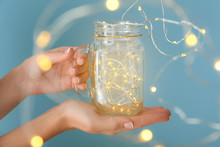 Female Hands With Glowing Garland In Jar On Color Background