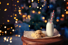 Fresh Chocolate Chips Cookies With Milk For Santa On Wooden Table, With Dark Background Of Xmas Tree And Space For Text