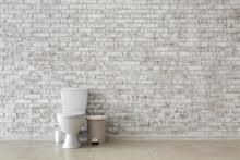 Toilet Bowl Near Light Brick W...