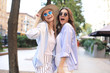Two young smiling hipster women in summer clothes posing on street.Female showing positive face emotions.