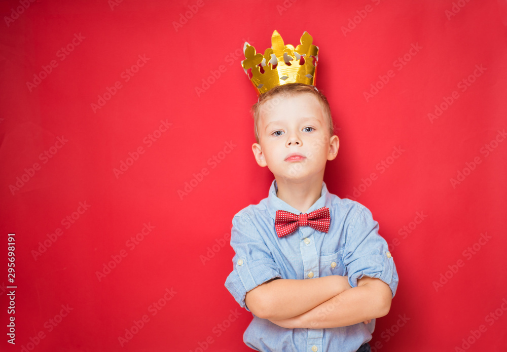 Fototapeta Happy education and childhood concepts with an adorable 6-year old boy holding a golden king crown on his head as a wise spoiled child, red background