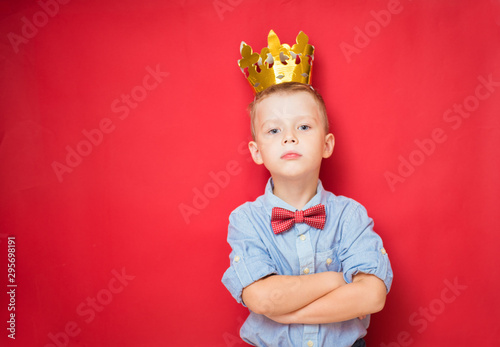 Happy education and childhood concepts with an adorable 6-year old boy holding a golden king crown on his head as a wise spoiled child, red background