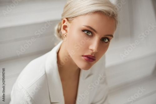 Slika na platnu A fashionable young woman with perfect blond hair and perfect trendy makeup in an elegant white suit posing in studio