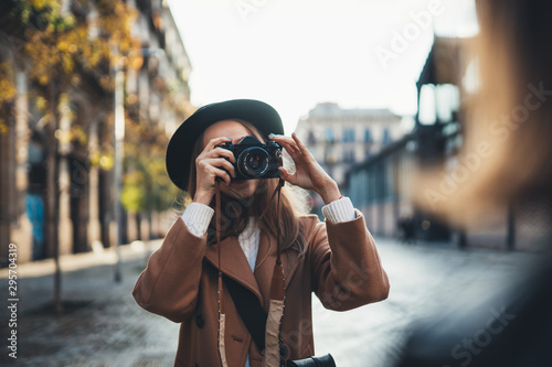 Obraz Outdoor smiling lifestyle portrait of pretty young woman having fun in sun city Europe autumn with camera travel photo of photographer Making pictures in glasses and hat with girlfriends - fototapety do salonu