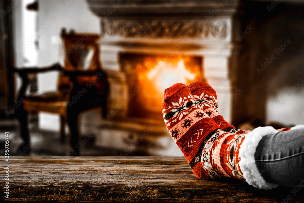 Fototapety, obrazy: Christmas socks with woman legs on wooden board of free space for your decoration and blurred background of fireplace