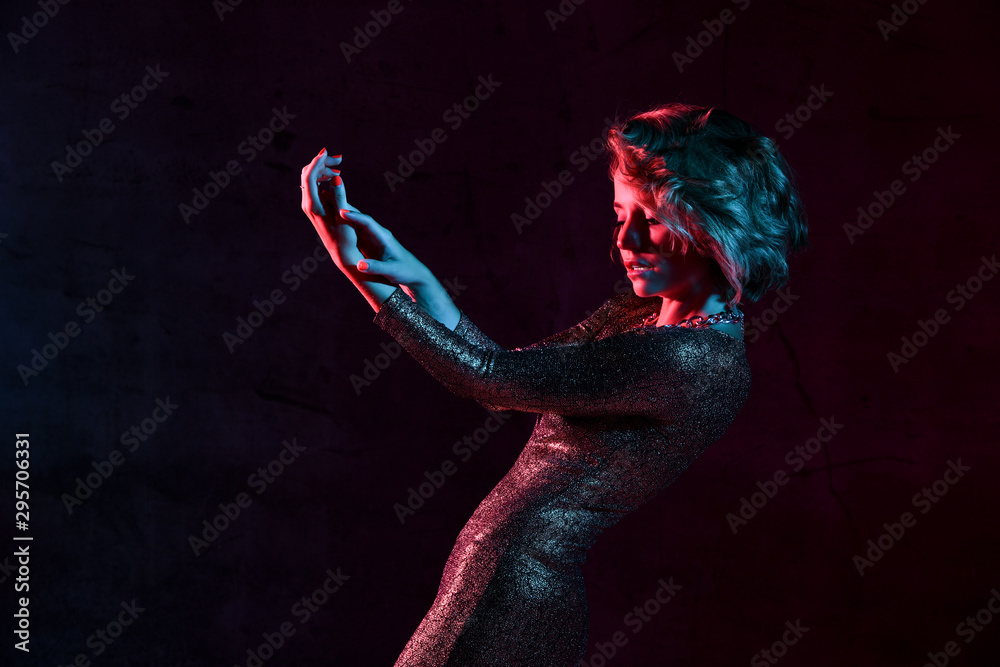 Fototapety, obrazy: Attractive young girl in a tight shiny dress in the studio with color filters.