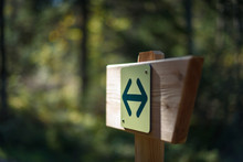 Hiking Sign With Two Opposite Arrows, Mounted On A Wooden Signpost In The Forest, With Blurred Trees And Leaves In The Background