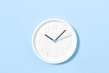 White Wall Clock On Pastel Blu...