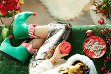 Trendy Woman In Funny Christmass Elf Shoes On Divan