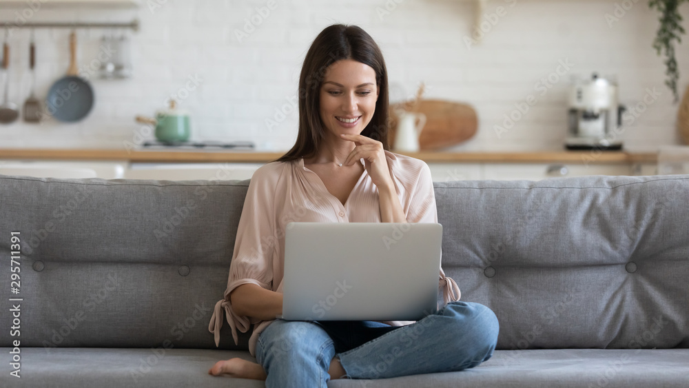 Fototapeta Smiling young woman using laptop, sitting on couch at home