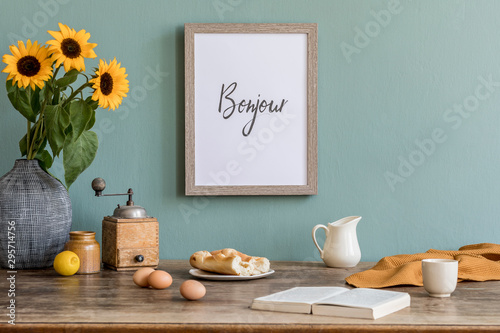 Fotografie, Obraz  Stylish and sunny interior of kitchen space with wooden table, brown mock up photo frame, breakfast and sunflowers