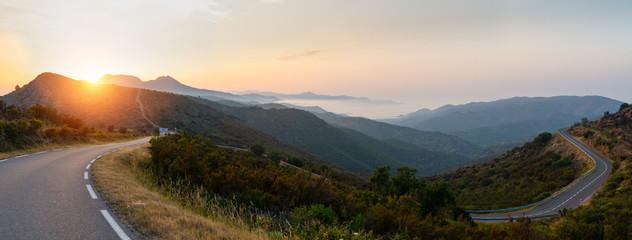 Mediterranean sea coast road into mountains horizon in summer with beautiful bright sun rays