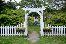 A White Wooden Arbour Or Arbor Erected Over A Well Worn Foot Path To A Flower And Shrub Garden. The White Latticework Is Covered In Vines. Two Boxes Of Pink Flowers Hangs From A White Picket Fence.