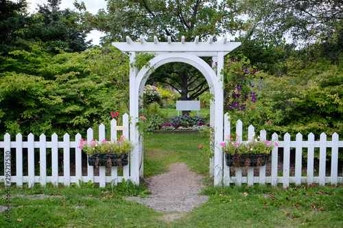Fotografiet A white wooden arbour or arbor erected over a well worn foot path to a flower and shrub garden