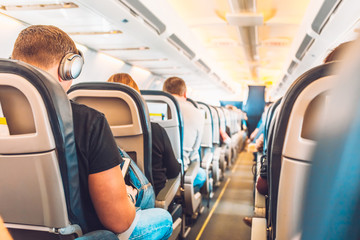 Passengers flying in armchairs in the cabin - economy class travel