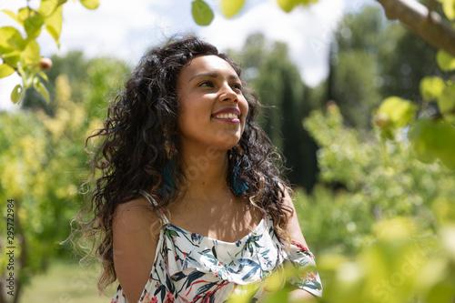 Mujer joven latina de piel morena y cabello largo y rizado sonriendo en entorno Canvas Print