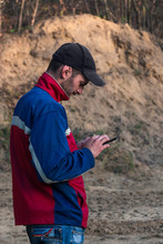 Man With A Phone And A Cigarette Walks In A Sand Quarry