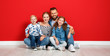 canvas print picture - happy family mother father and children daughter and son  near an   red wall