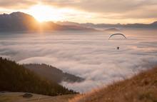 Man Paragliding Above The Clouds At Sunset, Salzburg, Austria
