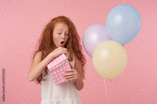 Studio photo of lovely redhead female kid in elegant dress celebrating holiday, unpacking gift box with excited face, posing over pink background with colored ballons