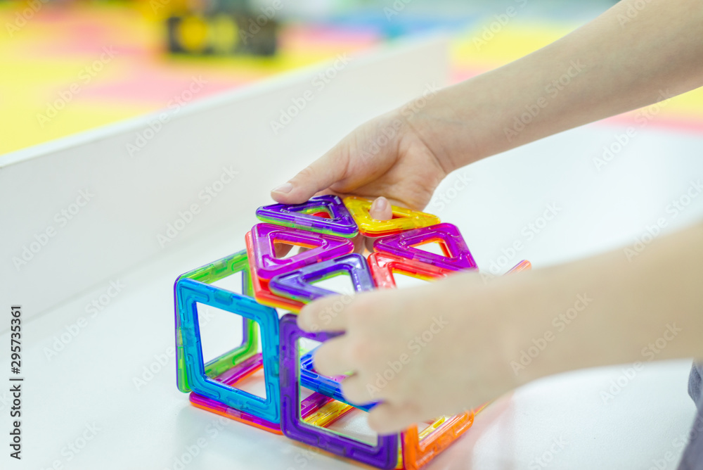 Fototapety, obrazy: Hands of a boy assemble a magnetic constructor.