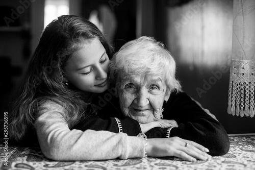 Elderly grandmother with her little girl granddaughter. Portrait black-and-white.