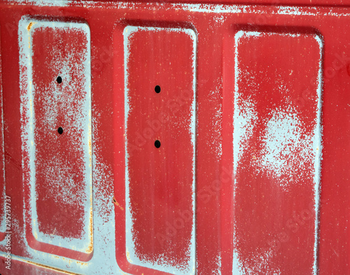 Faded paint on a red truck bed.