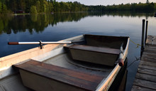 A Rowboat Tied To A Dock On A Lake.