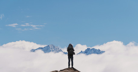 a man with backpack standing on mountain top, with snow mountains over clouds. Success, achievement and life goal concept