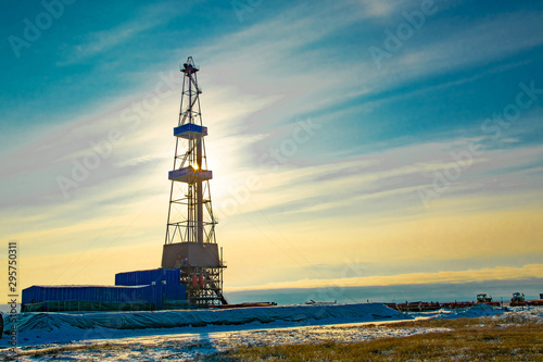 Fototapeta Oil and gas drilling rig in the northern tundra. The beginning of winter in the Arctic. The sun sparkles through the oil derrick. obraz