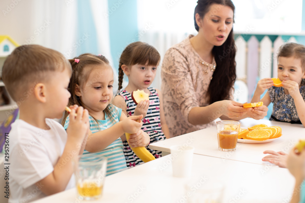 Fototapety, obrazy: Children and carer together eat fruit as a snack in the kindergarten, school or daycare